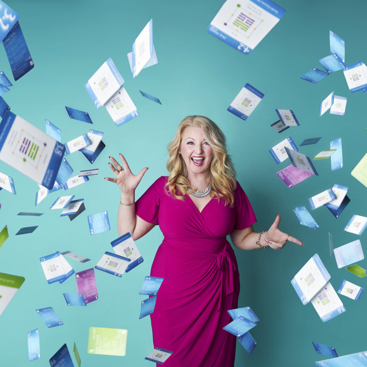free resources for business owners - NewSky Consulting - A photo of Katrina Johnson in a pink dress with cards flying through the air