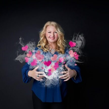 Team Development and Coaching - NewSky Consulting - Katrina Johnson with her arms open holding pink hearts